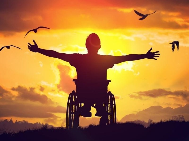 disabled man in wheelchair arms stretched out towards the sky
