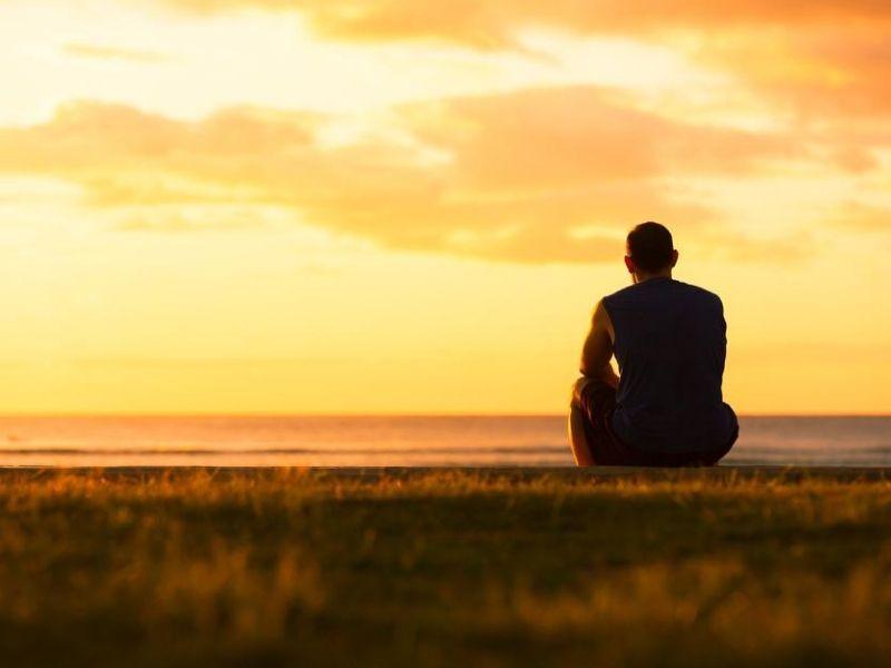 man sitting outdoors watching sunset