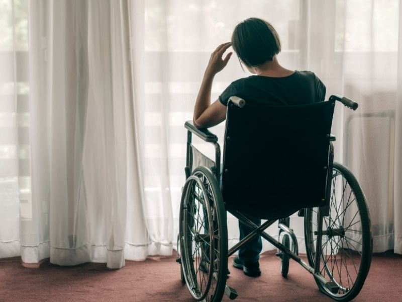 Depressed sad woman in worn wheelchair looking out the window